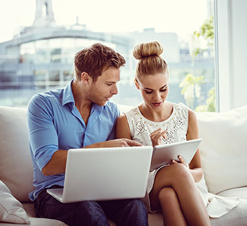 Man and Woman sitting on couch shopping online